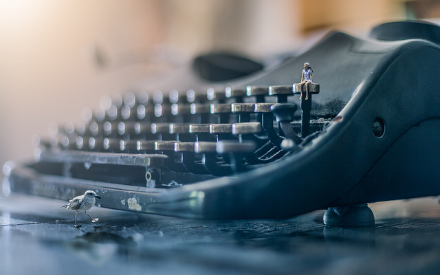 Close up of a typewriter with a small person sitting on a key in the top row and a bird in the foreground