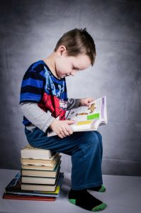 Young Child sitting on a stack of books reading a book