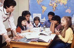 Teacher standing by a table containing 6 young students with books and a map