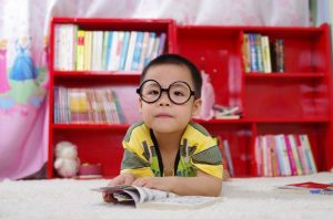 Student wearing glasses and reading a book