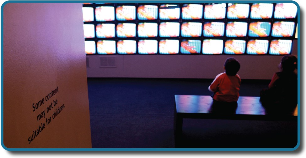 """Children sit in front of a bank of television screens. A sign on the wall says, """"Some content may not be suitable for children."""