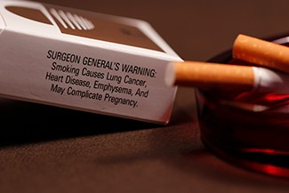 """A photograph shows pack of cigarettes and cigarettes in an ashtray. The pack of cigarettes reads, """"Surgeon general's warning: smoking causes lung cancer, heart disease, emphysema, and may complicate pregnancy."""
