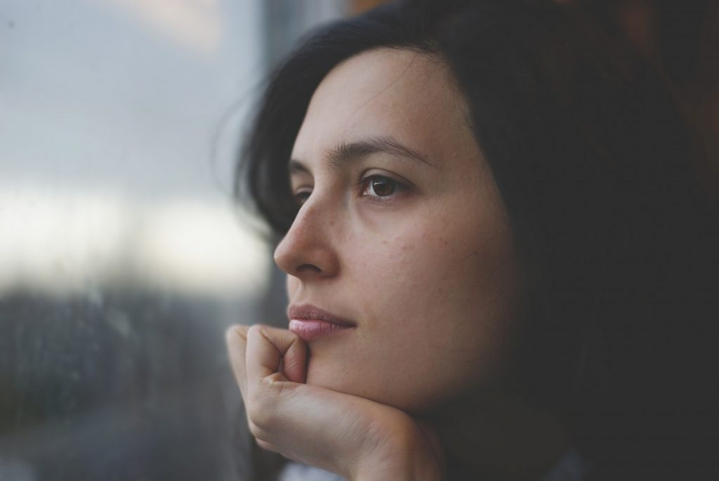 woman staring off into window with hand on chin
