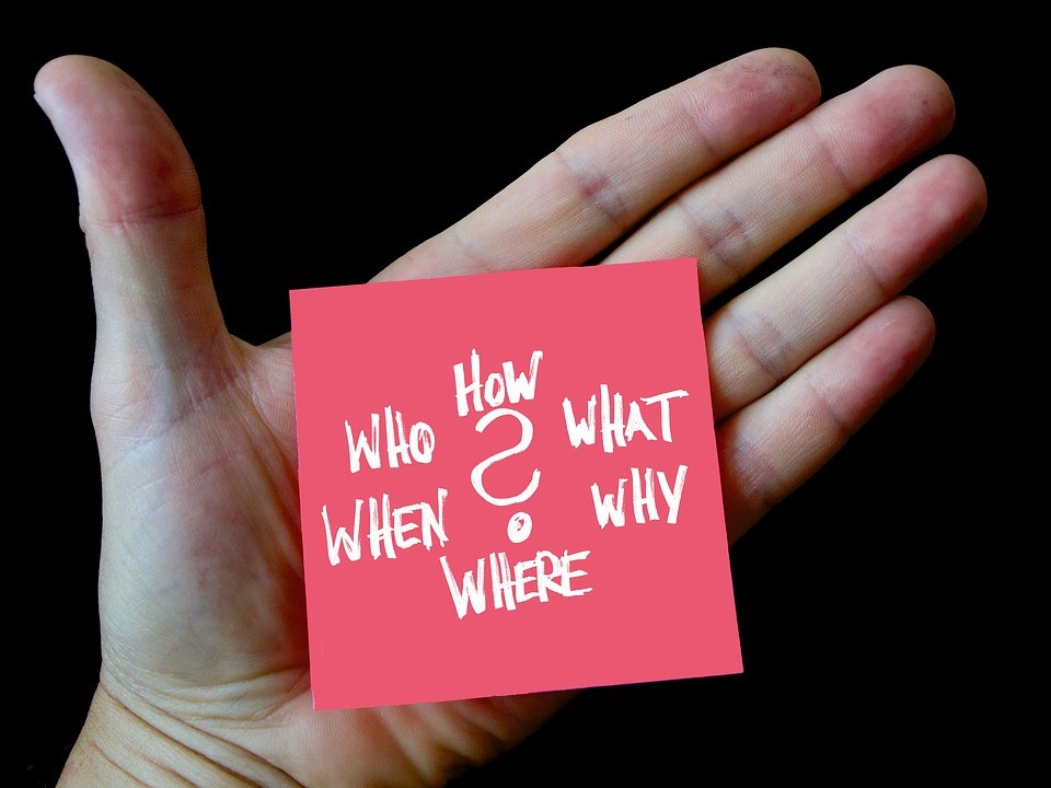 """hand holding a post-it note that says """"who, how, what, when, why, where"""""""