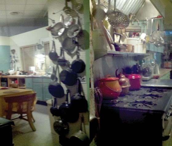 picture of a kitchen with many pots and pans organized on a pegboard
