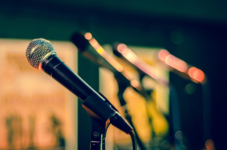 a row of microphones on a stage