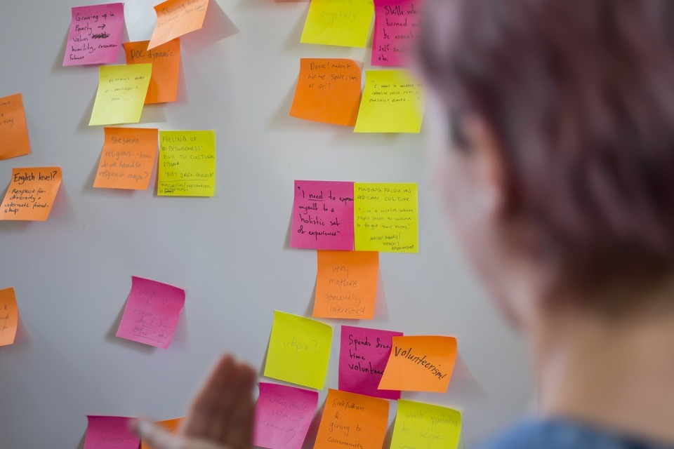 man staring at rows of post-it notes on the wall