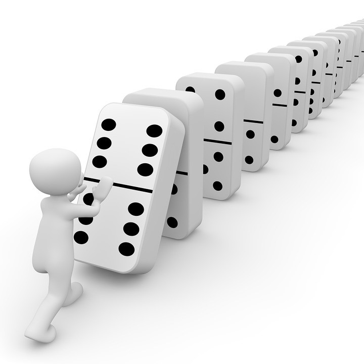 white 3-d cartoon knocking over a row of dominoes