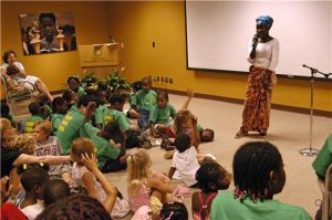 an woman speaking to a group of children in a room