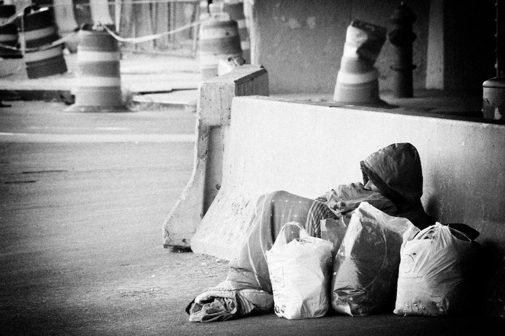 a homeless man lays under a blanket on the street with bags of items around