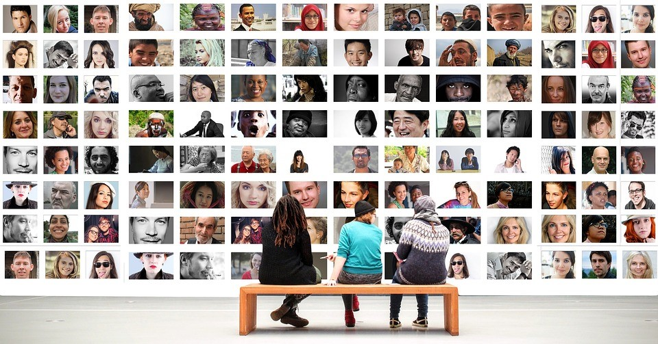 three people sitting on a bench in front of a wall composed of different people's photographs