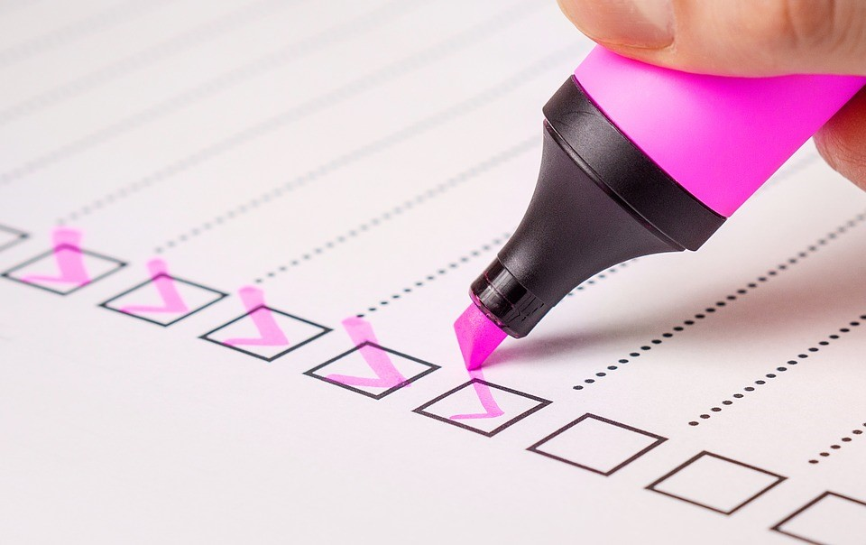 checking off checkmarks on a paper with a pink highlighter