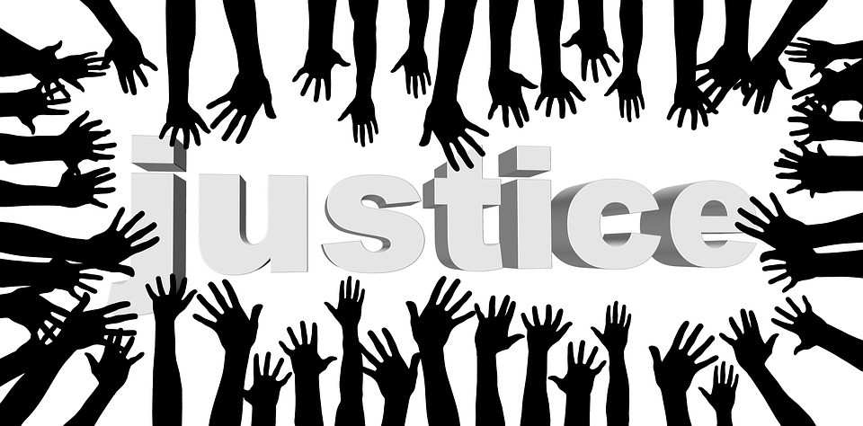 drawn black arms reaching towards the word justice written in grey text on a white background
