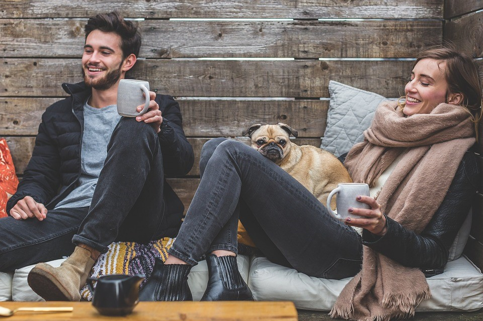two white people and a dog lounging with coffee