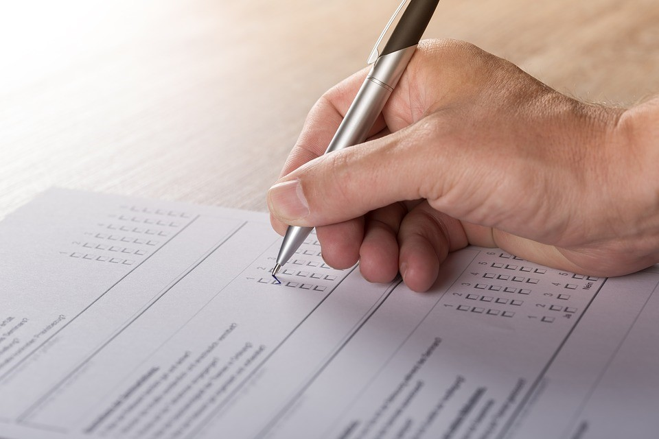a person checking boxes in a paper survey with a pen