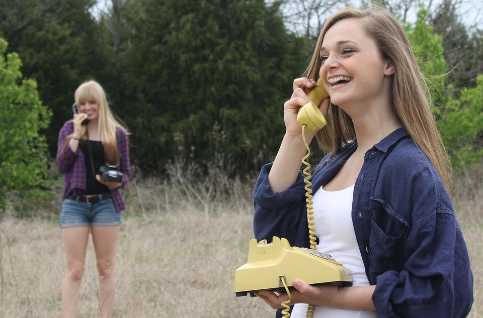 two girls in a field holding phones and laughing