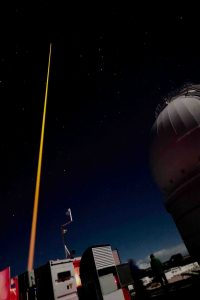 Night sky with orange-gold laser shooting vertically