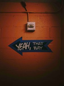 """Arrow pointing left painted on wall with caption """"Yeah, that way"""""""