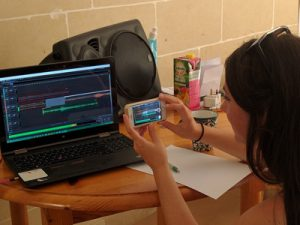 A student in a fieldschool videotapes her edits of an audio ethnography.
