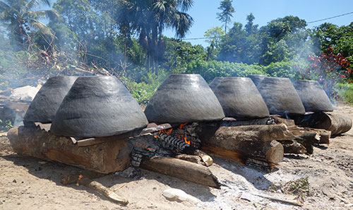 Image of clay cooking pots on a fire in Suriname; the design is similar to the culinary shoe pot.