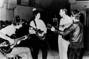 Black and white photographic image of the Beatles practicing.