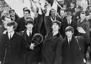 Black and white photographic image of the Beatles arriving at JFK airport.
