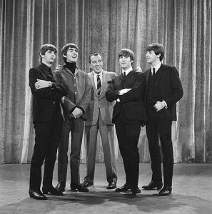 Black and white photographic image of the Beatles standing with Ed Sullivan.