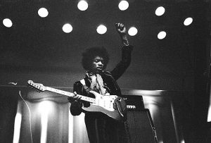 Black and white photo of Jimi Hendrix playing guitar live at a venue.