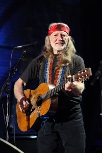Color photograph of Willie Nelson playing guitar on stage (2009)