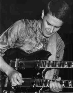Black and white photo of John McLaughlin playing a double necked guitar