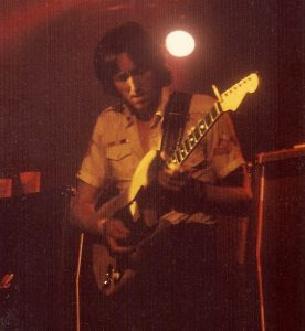 Colored photo of AH playing the guitar live - 1975