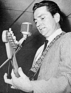 Black and white photograph of Willie Nelson playing guitar at The Grand Ole Opry