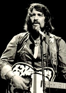 Black and white photograph of Waylon Jennings performing at a show live (1976)