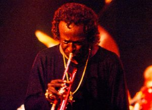 Color photo of Miles Davis playing the trumpet