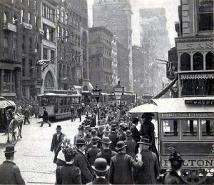 Black and White Image of New York City showing buildings, people, public transit.
