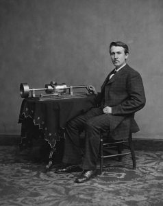 Black and white image of Thomas Edison seated next to the phonograph.