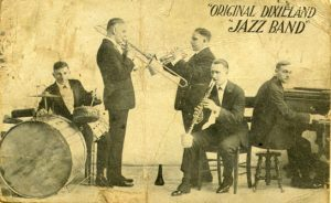 Yellowed promotional postcard featuring the original Dixieland Jass Band. The postcard shows five men each playing various instruments including: trombone, clarinet, trumpet, piano, and drums.