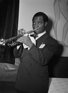 Black and white photographic image of Louis Armstrong playing the trumpet.