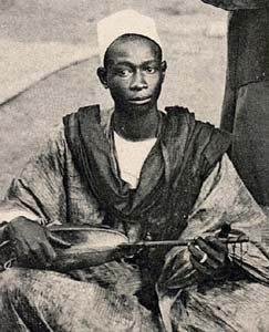Image of a black man seated wearing robe-like clothing.