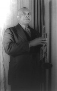 Black and white photographic image of W.C. Handy standing in a suit holding a trumpet.