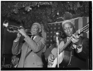 Black and white image of two men playing instruments. One is playing a trumpet. The other is playing an acoustic guitar.