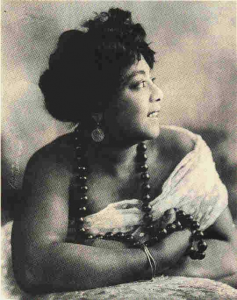 photographic image of Mamie Smith looking away from the camera, draped in a white fabric, wearing big black beads.
