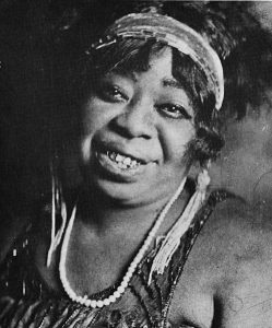 Black and white image of Ma Rainey wearing a headband and white necklace.