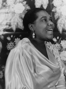 Black and white image of Bessie Smith in a silky top.