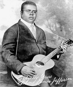 Black and white photographic image of Blind Lemon Jefferson wearing glasses, holding a guitar.