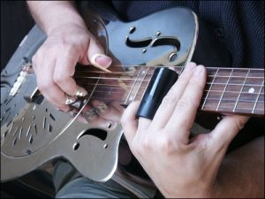 Color image of someone playing an electric slide guitar.