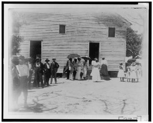 Black and white image of people outside a wooden building in dresses and suites.