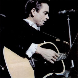 Color image of Johnny Cash with a guitar and microphone.