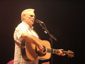 Color image of George Jones with a guitar and microphone.