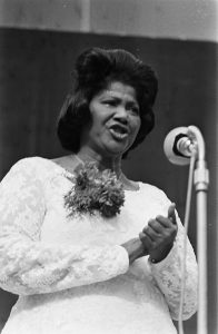 Mahalia Jackson in a white dress with a brooch of flowers singing into a microphone.